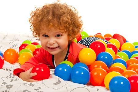 girl lying down: Feliz ni�a acostada en medio de muchas bolas de colores Foto de archivo