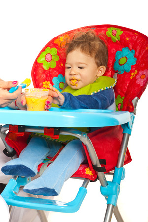 messy eater: Baby boy sitting in chair and being feeding by his mother with puree