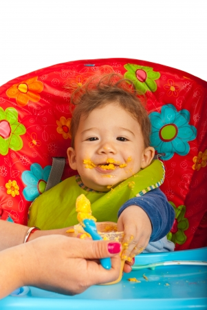 Messy baby boy eating puree and sitting in chair photo