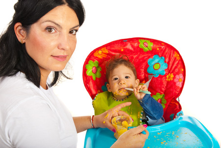 messy eater: Mother giving food to her messy baby boy against white background Stock Photo