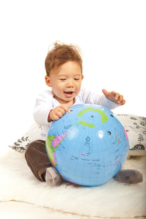 Cheerful baby boy playing with big world globe  photo