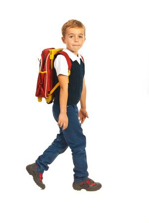 niños saliendo de la escuela: Longitud total de niño caminando a la escuela aislado en blanco