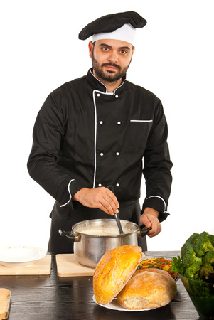 Chef man ready to put soup on a plate in kitchen photo