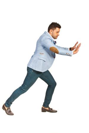 struggling: Business man pushing something on copy space isolated on white