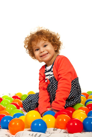 holding close: Happy toddler girl between colorful balls isolated on white