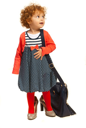 Toddler girl in big shoes carrying big moms bag and looking away isolated on white  photo