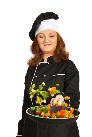Happy chef woman throwing vegetables in front of camera isolated on white background photo