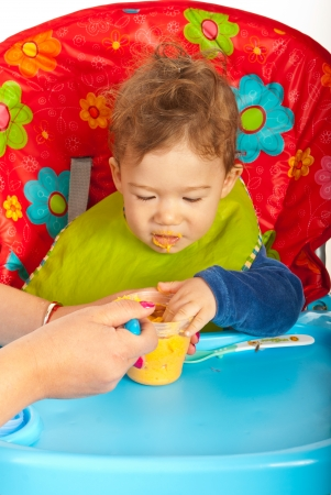 messy eater: Hungry baby eating puree and sitting on chair