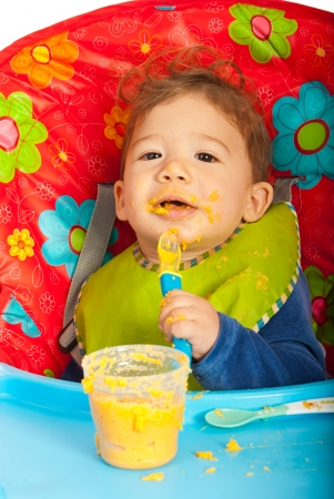 messy eater: Messy baby eating puree with spoon by yourself and sitting chair