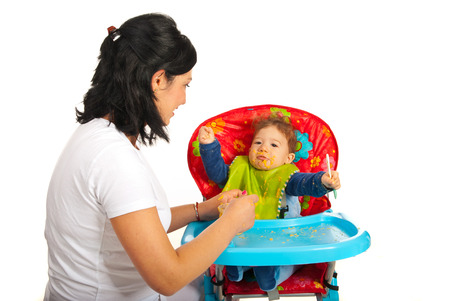 messy eater: Mother feeding baby with puree in their home Stock Photo