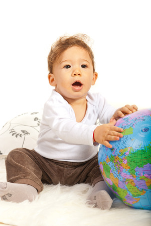 Amazed baby with world globe sitting on fur blanket photo