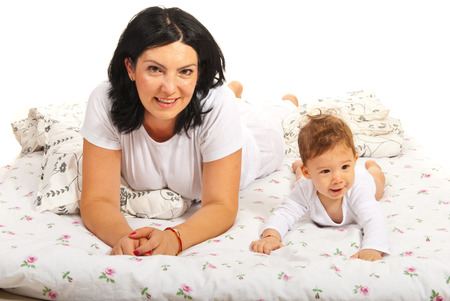 Mother and baby lying bed together against white background photo