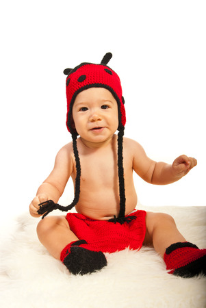 Happy baby boy in ladybug hat and boots sitting on fur blanket photo