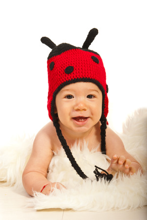 Happy baby with two teeth wearing ladybug hat and lying down photo
