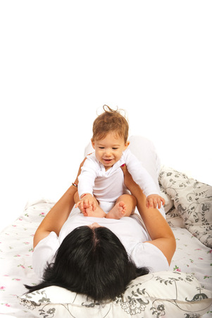 Mother and baby having fun in bed against white  photo