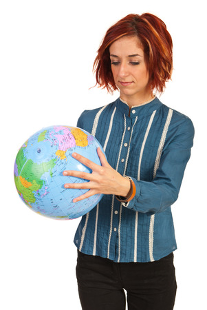 Woman looking on a world globe isolated on white background photo