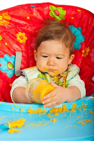 messy eater: Messy baby boy eating puree by yourself and sitting in chair