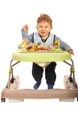 Funny baby boy running in a walker isolated on white background photo