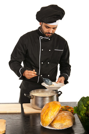 Chef man putting soup on plate from a big pot photo