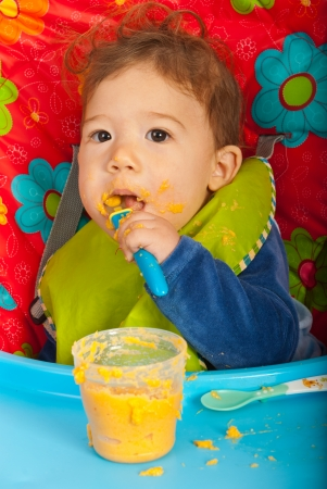 messy eater: Baby boy eating vegetables puree by yourself and sitting in chair