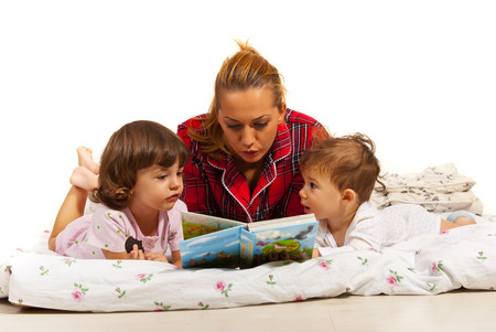 Mother reading story to her kids in bed before sleep photo