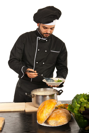 Chef male putting soup on plate from a big pot isolated on white background photo