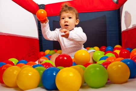 playpen: Baby boy sitting in playpen with colorful balls and throwing a orange ball Stock Photo