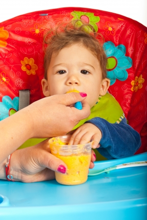 messy eater: Mother feeding baby boy with vegetables puree