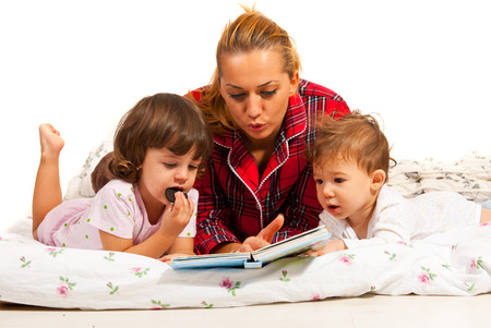 bedtime: Mother reading bedtime story to her  children  in bed Stock Photo