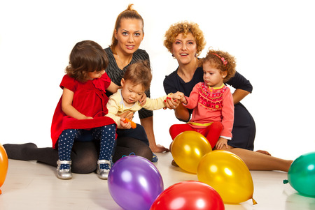 mom's house: Two mothers with their kids at party with balloons sitting on floor together