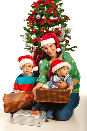 Happy mother with two boys sitting in front of Christmas tree with presents photo