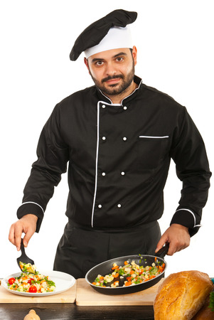 Chef male garnish vegetables on plate in kitchen photo