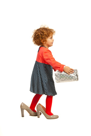 Funny little girl in big shoes carrying present isolated on white background photo