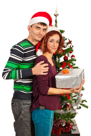 Couple holding Christmas present in front of tree photo