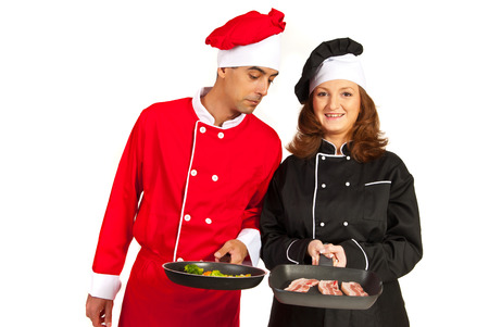 Funny chef looking with surprised face into his colleague woman frying pan photo