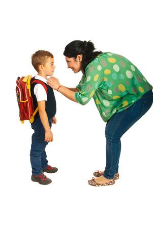 Madre preparare ragazzo per la scuola isolato su sfondo bianco