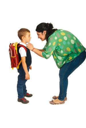 Mother prepare boy for school isolated on white background photo