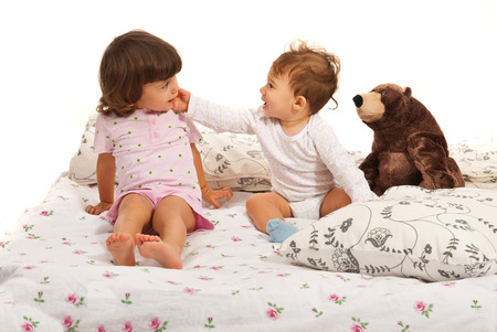 Happy baby boy touching toddler girl face in bed photo