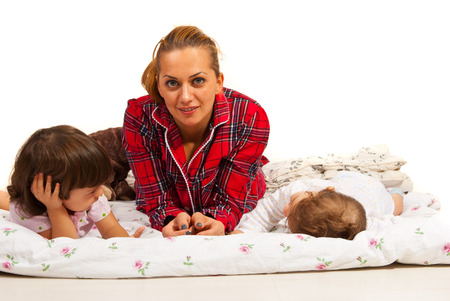 Happy mom lying down with her kids in bed photo