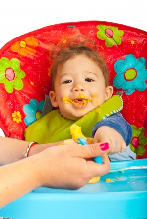 messy eater: Happy baby eating vegetables puree and sitting in chair