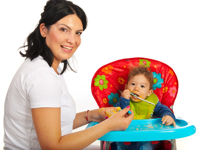 messy eater: Happy mom feeding her baby boy with vegetables puree