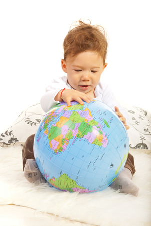 Baby boy sitting down and searching world globe photo