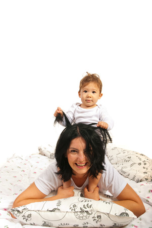 Baby boy playing with his mother hair in bed  photo