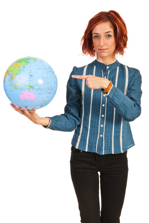 Business woman pointing to world globe isolated on white background photo