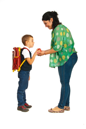 Mother giving apple to her son and prepare for school photo