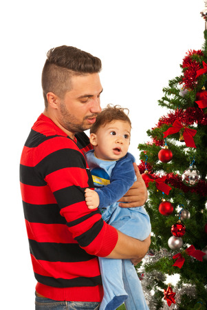 Father holding baby son and standing near Christmas tree photo