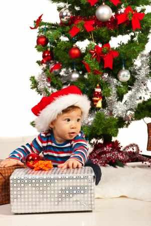 baby near christmas tree: Cheerful baby with Christmas present looking away and sitting near tree