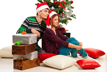Couple sitting near Christmas tree with presents and dreaming with open eyes  photo