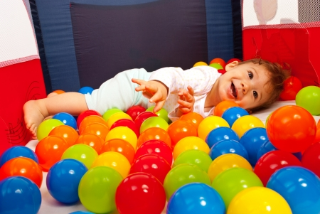playpen: Happy baby playing with balls inside playpen