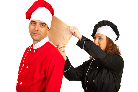 Chefs couple having fun and woman prepare to touching man with wooden board photo